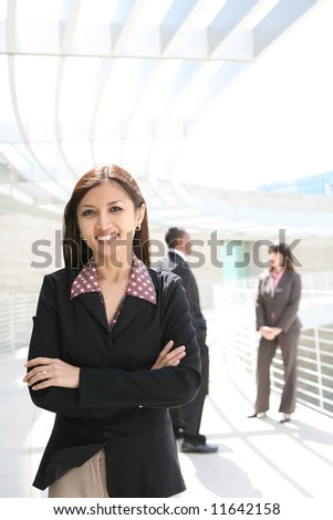 A pretty asian business woman on at company with co-workers in background - stock photo