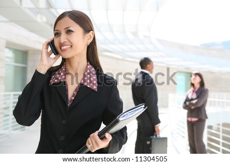 A pretty asian business woman on cell phone with co-workers in background - stock photo