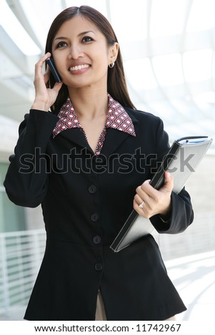 A pretty asian business woman on the cell phone - stock photo