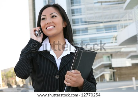 A pretty asian business woman on the cell phone outside office building