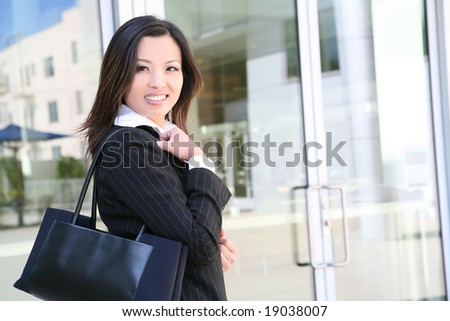 A pretty asian business woman outside office building - stock photo