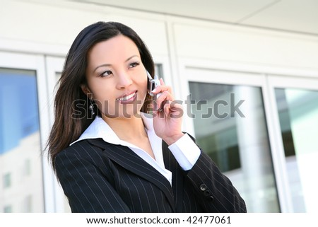 A pretty asian business woman outside office building on phone - stock photo
