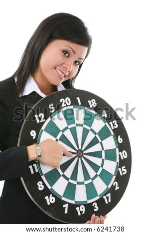 A pretty asian business woman pointing to the bullseye on a target board - stock photo