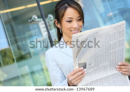 A pretty asian business woman reading the newspaper at office building - stock photo
