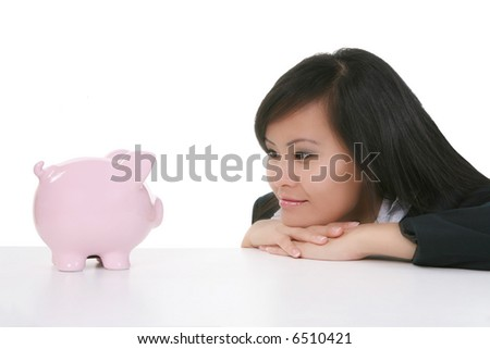 A pretty asian business woman staring at a piggy bank