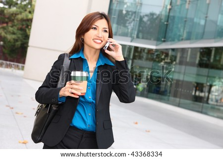 A pretty asian business woman walking with coffee talking on phone - stock photo