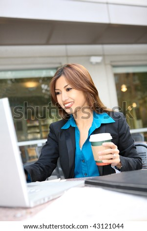 A pretty asian business woman working on her laptop computer - stock photo