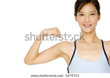 A pretty asian girl flexes one arm on white background - stock photo