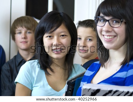 A pretty Asian girl with a group of her fellow schoolmates, stop and smile big for the camera. - stock photo