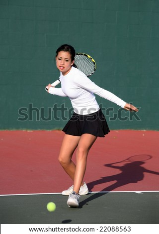 A pretty asian teenage girl playing tennis - stock photo