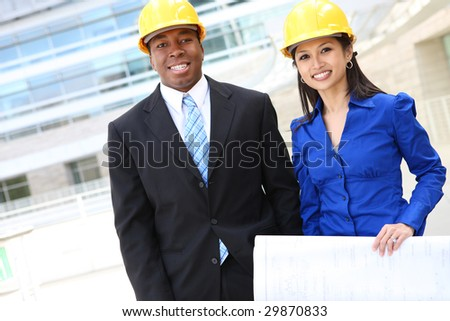 A pretty asian woman and african man working as architects on a construction site - stock photo