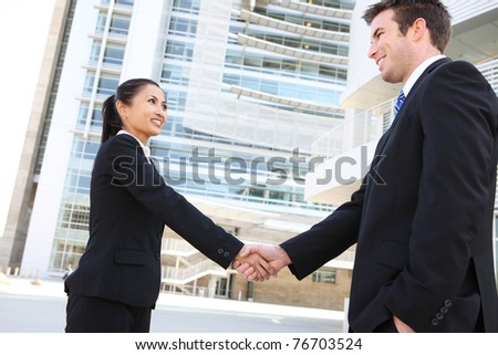A pretty asian woman handshake with handsome man at office building - stock photo