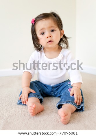 A pretty baby girl sitting with a white t-shirt - stock photo