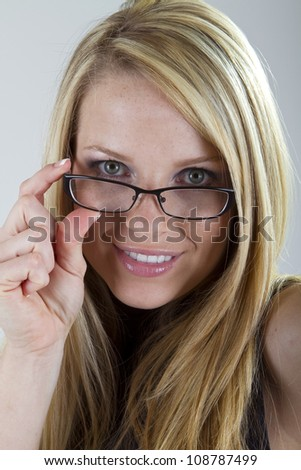 A pretty blond girl peeks over her eyeglasses and smiles into the camera.