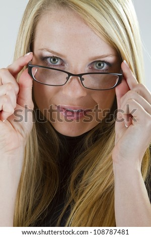 A pretty blond girl peers into the camera as she starts to put on her glasses. - stock photo