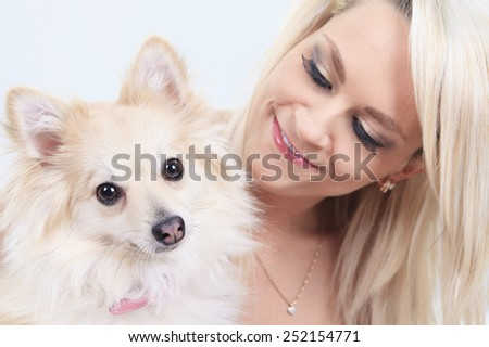 A pretty blond girl sitting with is dog on the sofa - stock photo