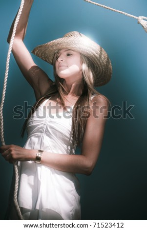 A Pretty Blond Young Woman Wearing A Straw Cowboy Hat Twirling A Lasso Against A Blue Sky Background - stock photo