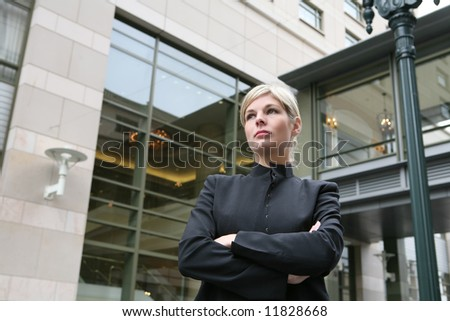 A pretty blonde business woman in downtown urban district - stock photo