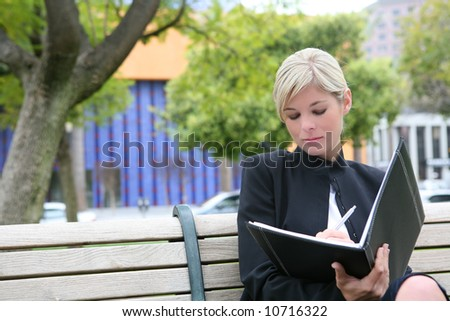 A pretty blonde business woman with notebook outside
