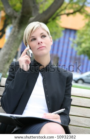 A pretty blonde business woman with notebook outside - stock photo