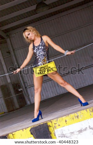A pretty blonde model is striking a sexy pose behind a private property sign with her short skirt raised high behind the sign, looking at viewer - stock photo
