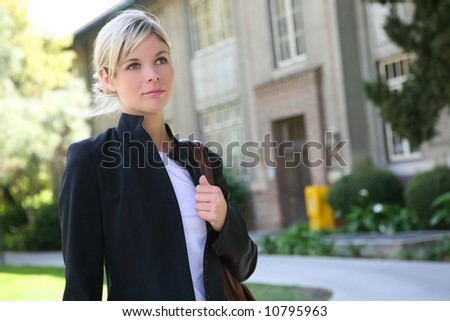 A pretty blonde student at her college walking to class - stock photo