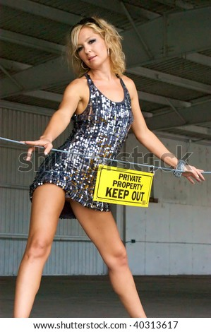 "A pretty blonde wearing a short dress has her hip pushed out and is looking down at viewer from loading dock behind a sign that reads ""Private property keep out"". - stock photo"