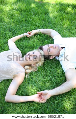 A pretty blonde woman and handsome man in love in the park - stock photo
