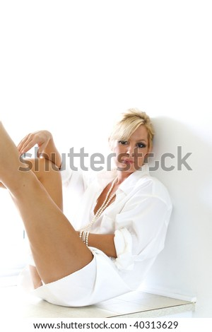 a pretty blonde woman is looking directly at the viewer as she reclines on a window seat wearing a man's white dress shirt and pearls, lit by window light - stock photo