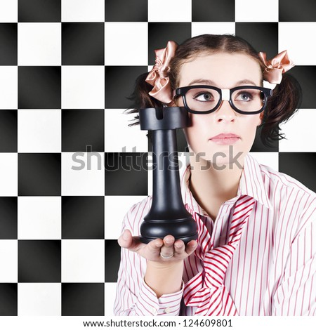 A pretty brainy nerdy young woman in glasses holds an outsize chess piece in her hand against a black and white chessboard backdrop advocating intelligent marketing with prior planning and strategy - stock photo