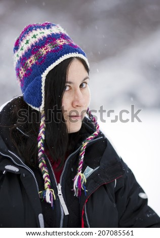 A pretty brunette girl in a colorful hat smiles during a light snow shower. - stock photo