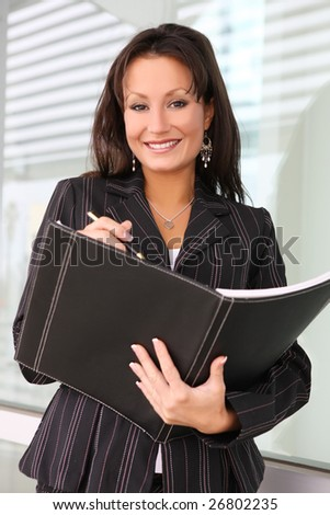 A pretty business woman at the office with notebook