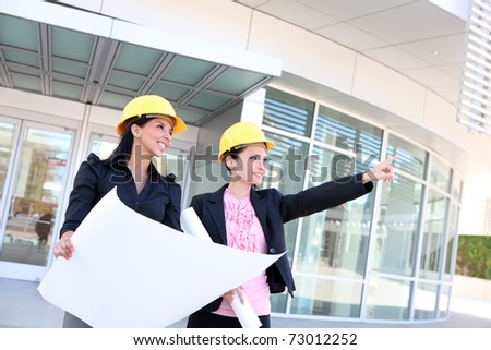 A pretty business woman construction team at office building with plans - stock photo