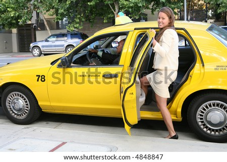 A pretty business woman getting into a taxi cab