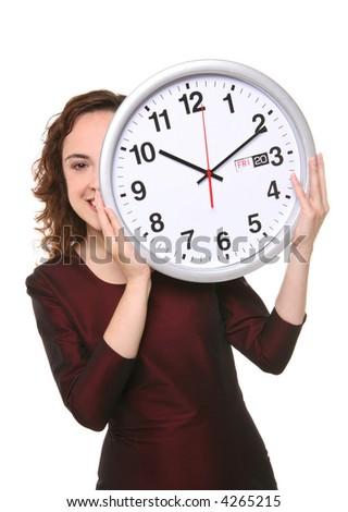 A pretty business woman hiding behind a clock - stock photo