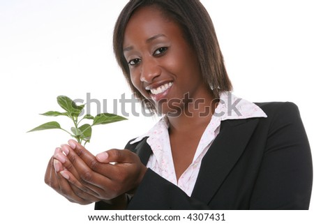 A pretty business woman holding a growing plant - stock photo