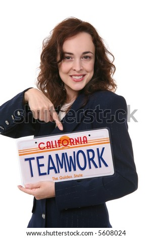 A pretty business woman holding a teamwork license plate - stock photo