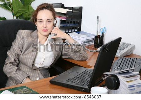 A pretty business woman in the office on the phone