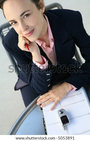 A pretty business woman making an entry into her calendar - stock photo