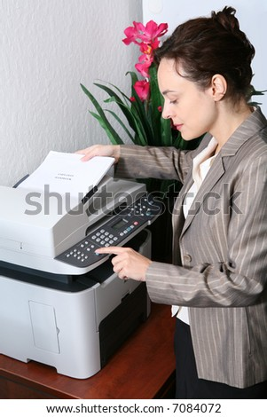 A pretty business woman making copies on the photocopy machine - stock photo