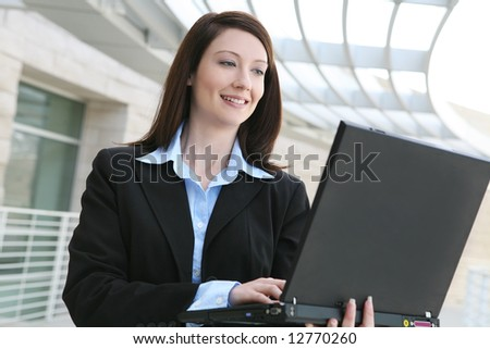 A pretty business woman on laptop computer  at office building - stock photo