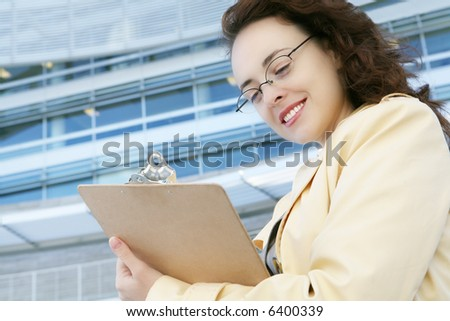 A pretty business woman outside her office building - stock photo