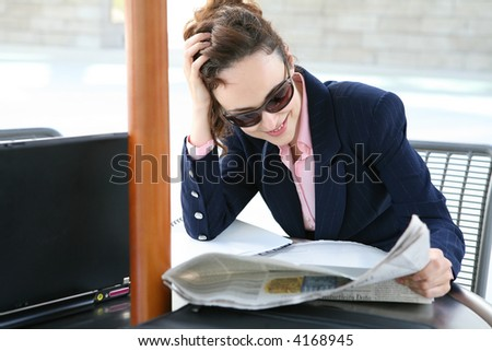 A pretty business woman reading a newspaper - stock photo