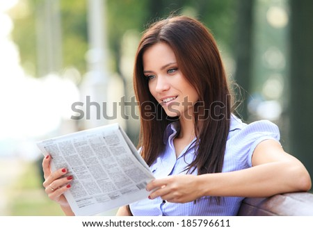 A pretty business woman reading newspaper outside in the park  - stock photo