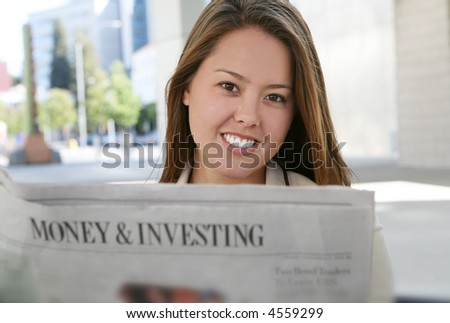 A pretty business woman reading the newspaper - stock photo