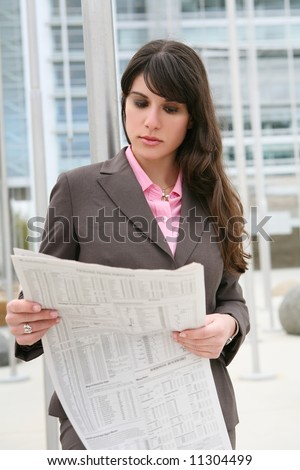 A pretty business woman reading the newspaper outside company - stock photo