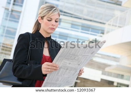 A pretty  business woman reading the newspaper outside her company - stock photo