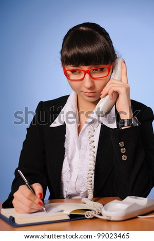 A pretty business woman sitting at table and talking - stock photo