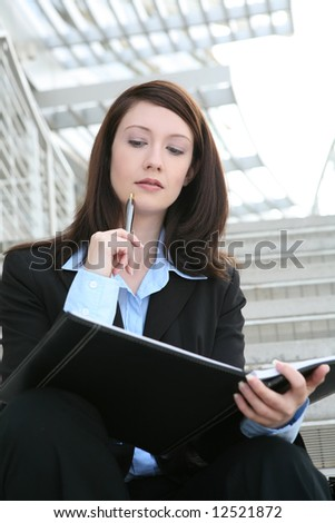 A pretty business woman sitting on the stairs at company - stock photo