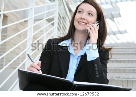 A pretty business woman sitting on the stairs on phone at company - stock photo